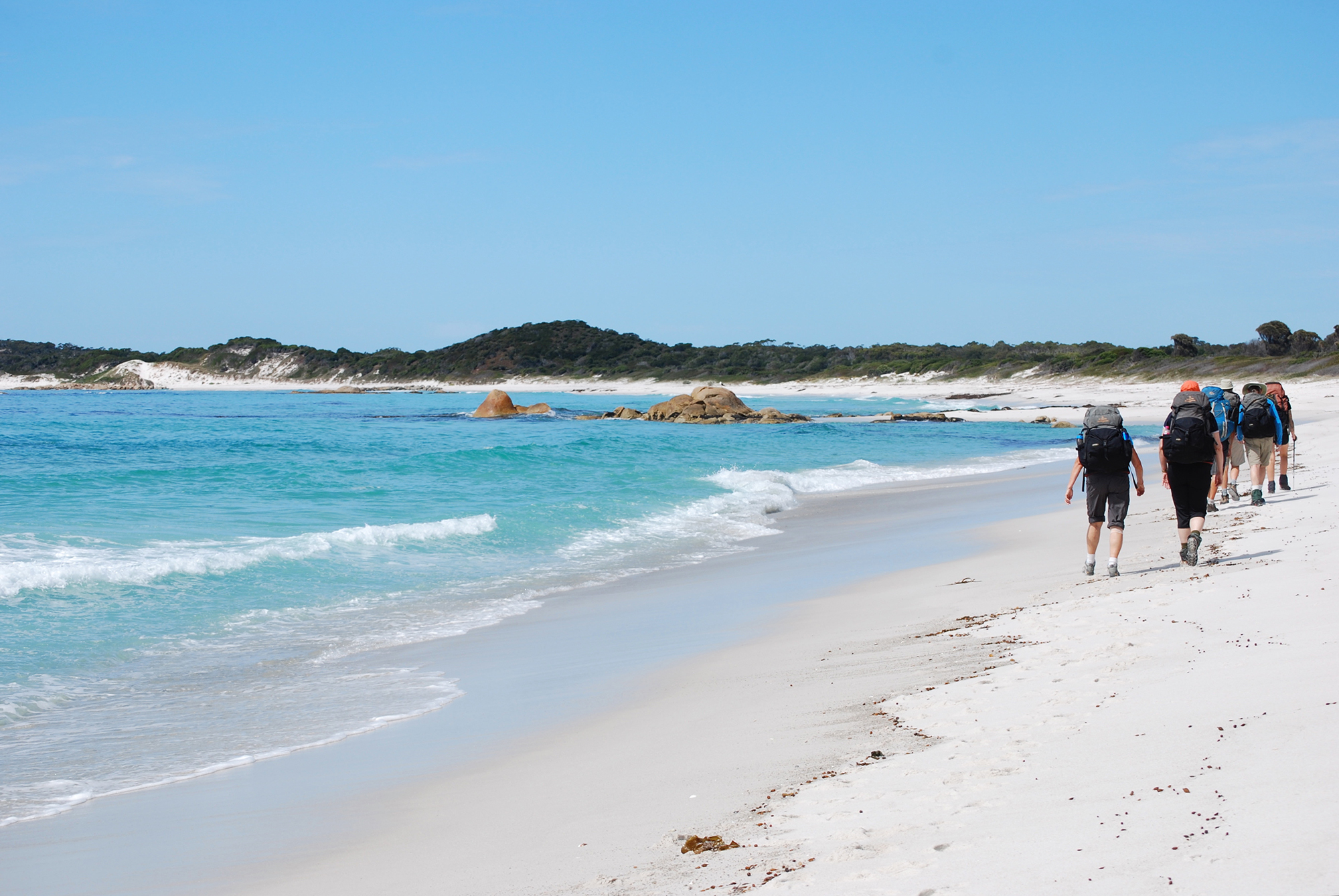 Bay of Fires tour participants walk along the beach on a sunny day