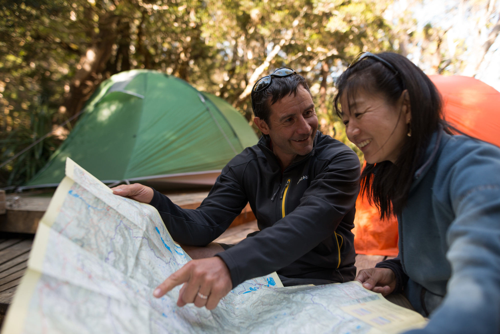 Two walkers looking at the Overland Track map siting infront of tents and plaforms at Waterfall Valley campsite