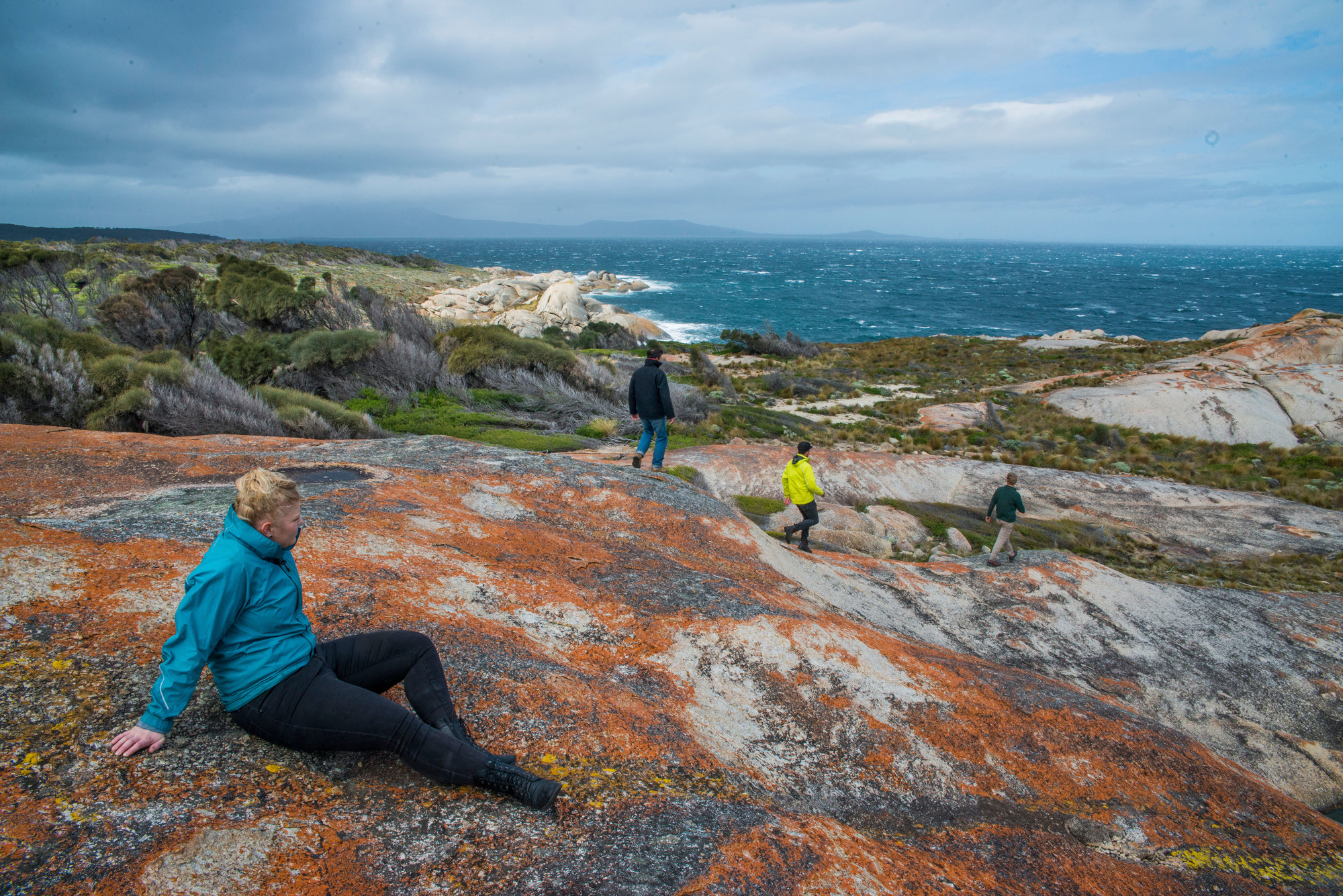 Trousers Point Walk, people sitting and walking on granite boulders, overlooking ocean, Flinders Island