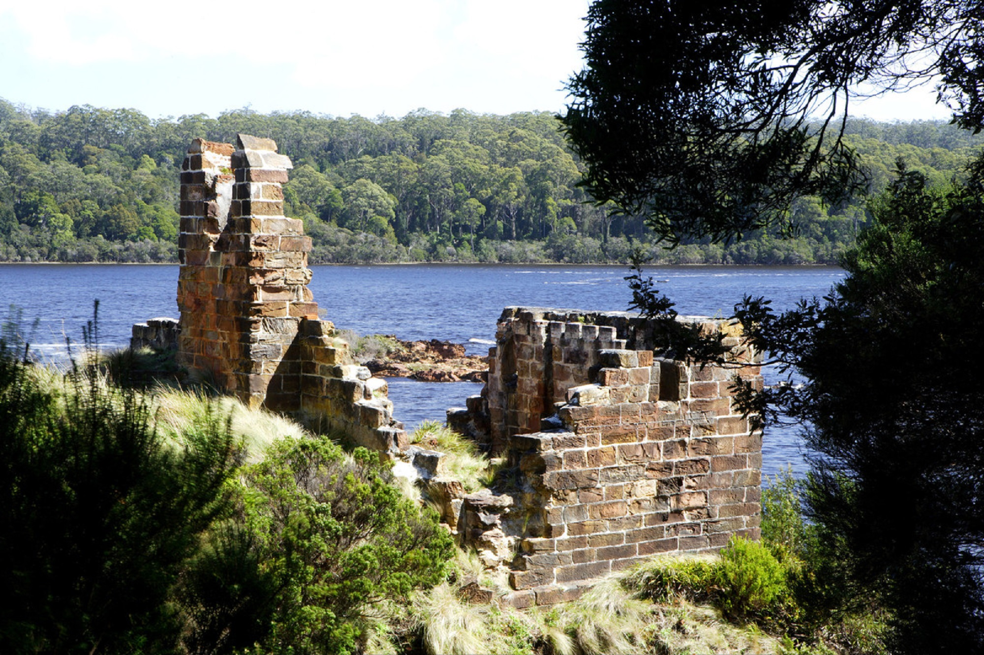 Image of the remains of an old brickk structure on the edge of Macquarie Harbour.