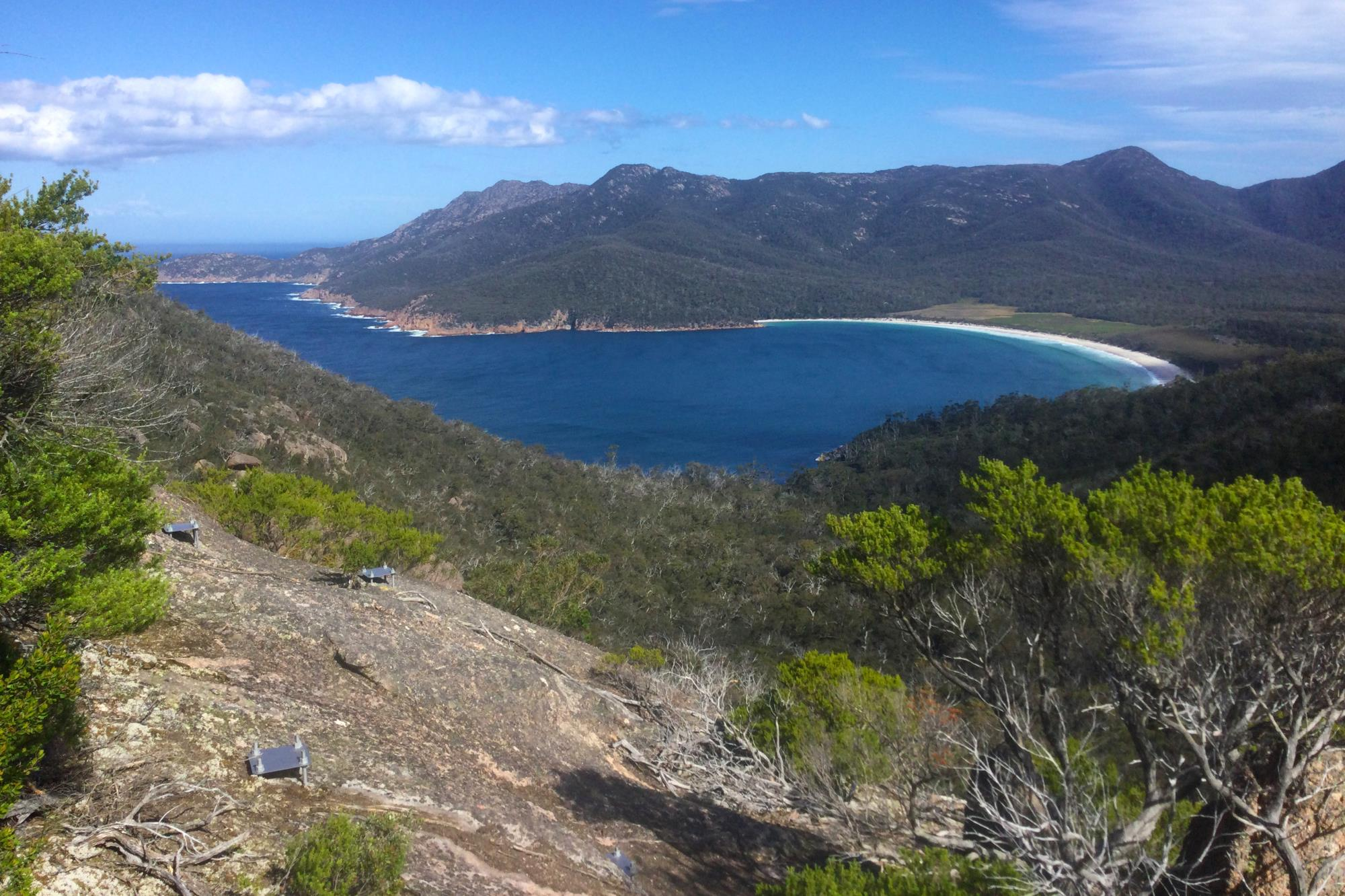 Metal fottings embedded in granite are part of the new walkway works. This image shows the footings with a view of beautiful Wineglass Bay on a fine sunny day in the background.