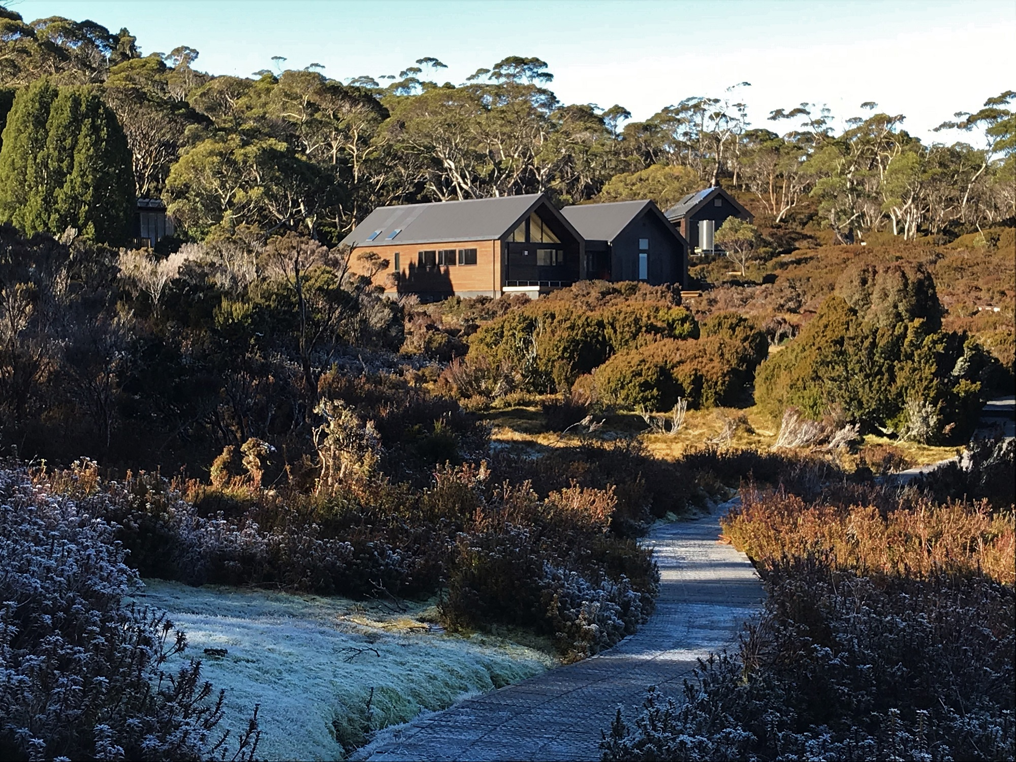 The new Waterfall Valley hut on the Overland Track bathed in sun with snow on the track leading to the hut.